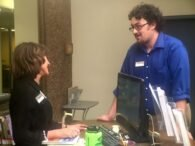 Social worker intern, Brendan Haggerty, talks with library staff.