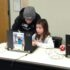Teen volunteers assist Minecraft players.